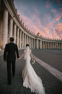 newlyweds walk through historic building at sunset in italy