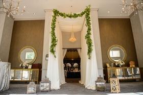 Wedding reception entrance tall ceiling drapery garland chandelier two mirrors buffet sideboard