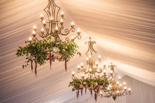 tented reception with drapery, chandeliers with greenery and florals