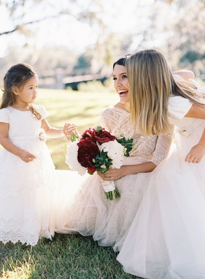 Bride in lace wedding dress playing with two flower girls in white dresses on lawn grass kneeling