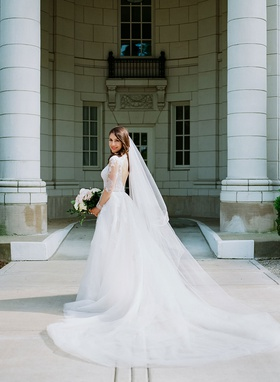 bride in low back long sleeve wedding dress monique lhuillier long hair down with veil white bouquet