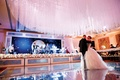 Bride and groom first dance on dance floor with crystal ceiling treatment and pink lighting