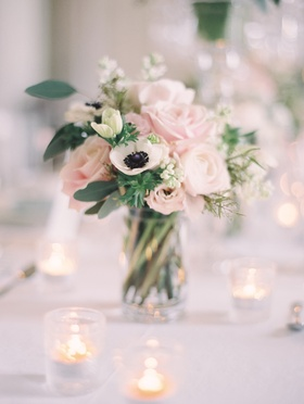 Wedding reception table with bouquet of blush roses, ivory anemones, and greenery