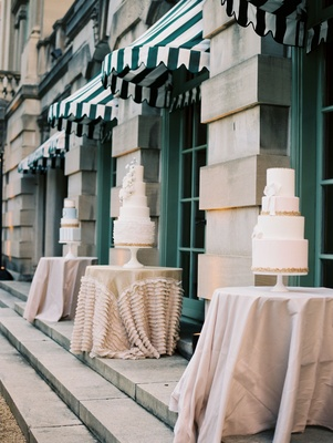 Wedding cakes displayed on small tables with linens at wedding reception outdoors by pool DC