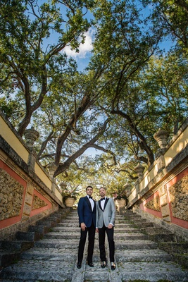 same-sex wedding gay couple, groom in navy tuxedo jacket, groom in grey tuxedo jacket on steps