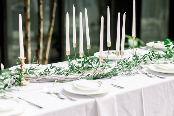 unique curved gold candelabra with white candles and greenery