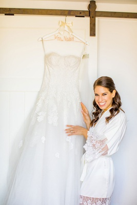 wedding dress monique lhuillier strapless lace floral applique hanging up on custom hanger ivory bow