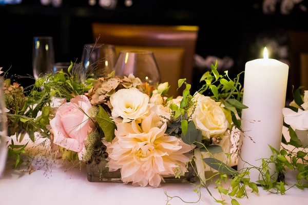 Wedding reception table with pink roses, dahlias, white roses, lisianthus, greenery, pillar candle