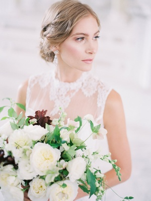 Bride in a JINZA Couture Bridal dress with chantilly lace, updo, bouquet of white flowers, greenery