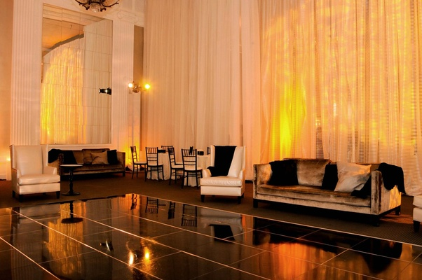 Comfortable couches around black tile dance floor and