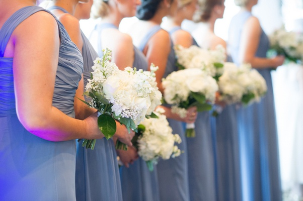 Bridesmaids in blue dresses at ceremony holding flowers
