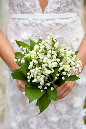 Bride holding lily of the valley wedding bouquet large engagement ring marchesa wedding dress
