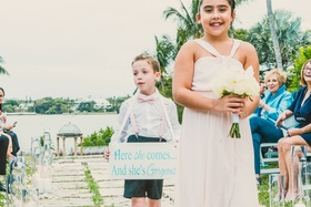 junior bridesmaid with small bouquet, ring bearer with shorts, suspenders, and bow tie carrying sign