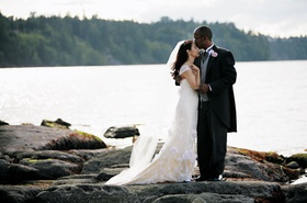 Bride in a Claire Pettibone lace gown and groom in black tails and grey vest on the beach