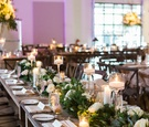 candlelight and tall centerpieces with long wooden tables and greenery