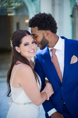 bride in white wedding gown with her groom in bright blue tuxedo orange and blue tie pocket square