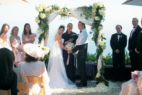Bride and groom under white and green altar