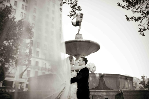 Black and white photo of couple with veil in wind