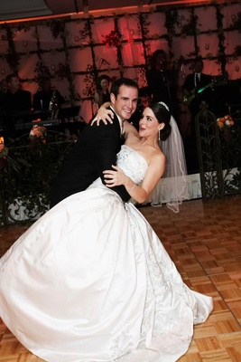Groom dips bride during first dance at wedding