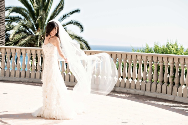 bride letting veil float in wind strapless beaded gown long southern california bel-air beach club