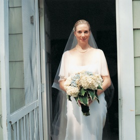 Bride holds bouquet with white and blue flowers