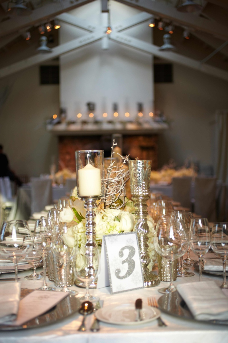 Silver bordered table number next to candlesticks