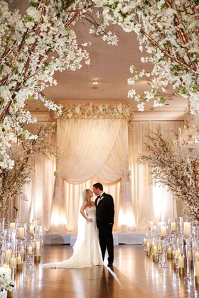 Bride in strapless Pnina Tornai dress, groom in black tuxedo, white fabric chuppah