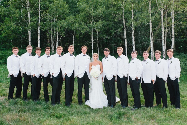 Bride in inbal dror wedding dress with groomsmen and groom in white tuxedo jackets bow ties