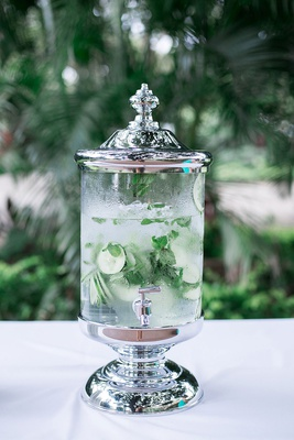 wedding ceremony outdoor drink dispenser with ice water mint leaves and cucumber slices