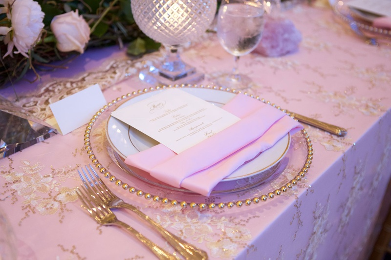 Pink wedding reception decor gold charger plate forks and linen accents candle votives