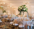 wedding reception ballroom wallpaper chandeliers crisscross chairs tall centerpiece greenery pink