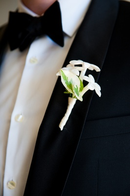 Groom in tuxedo wearing white stephanotis boutonniere