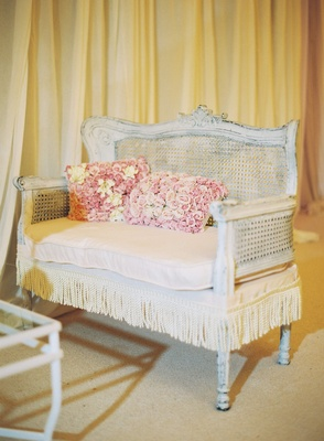 Antique white loveseat with fringe and rose pillows