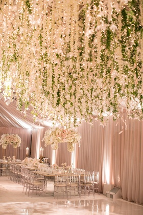 Wedding reception cascading flowers and greenery over white dance floor tent wedding reception