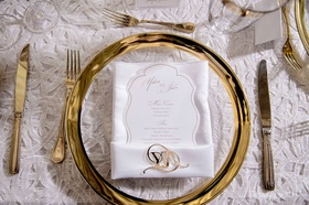 Gold charger plate with white menu and invitation with gold monogram accessory gold flatware white