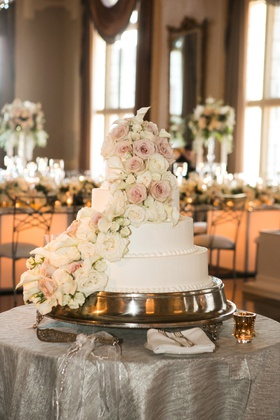 four tier white weddign cake with blush and white roses and calla lilies