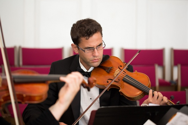 Man playing violin at church wedding ceremony