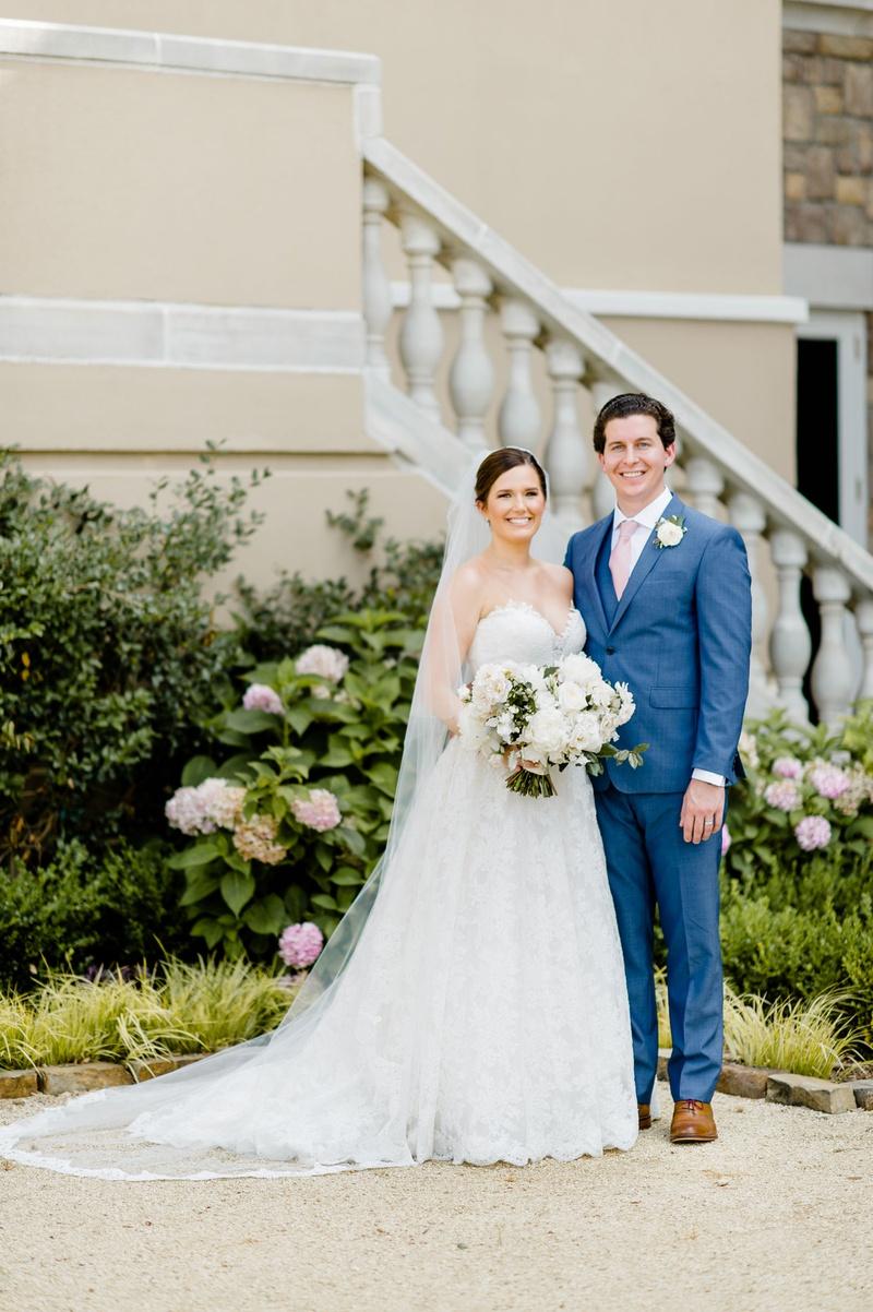 bride in strapless romona keveza wedding dress updo veil groom in blue suit vest pink tie brown shoe