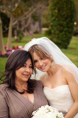 Bride smiles with mother of the bride in pleated dress