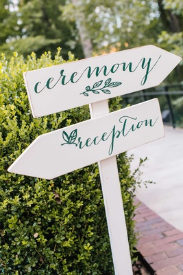 White wood post with ceremony and reception sign in modern calligraphy and leaf motif at wedding