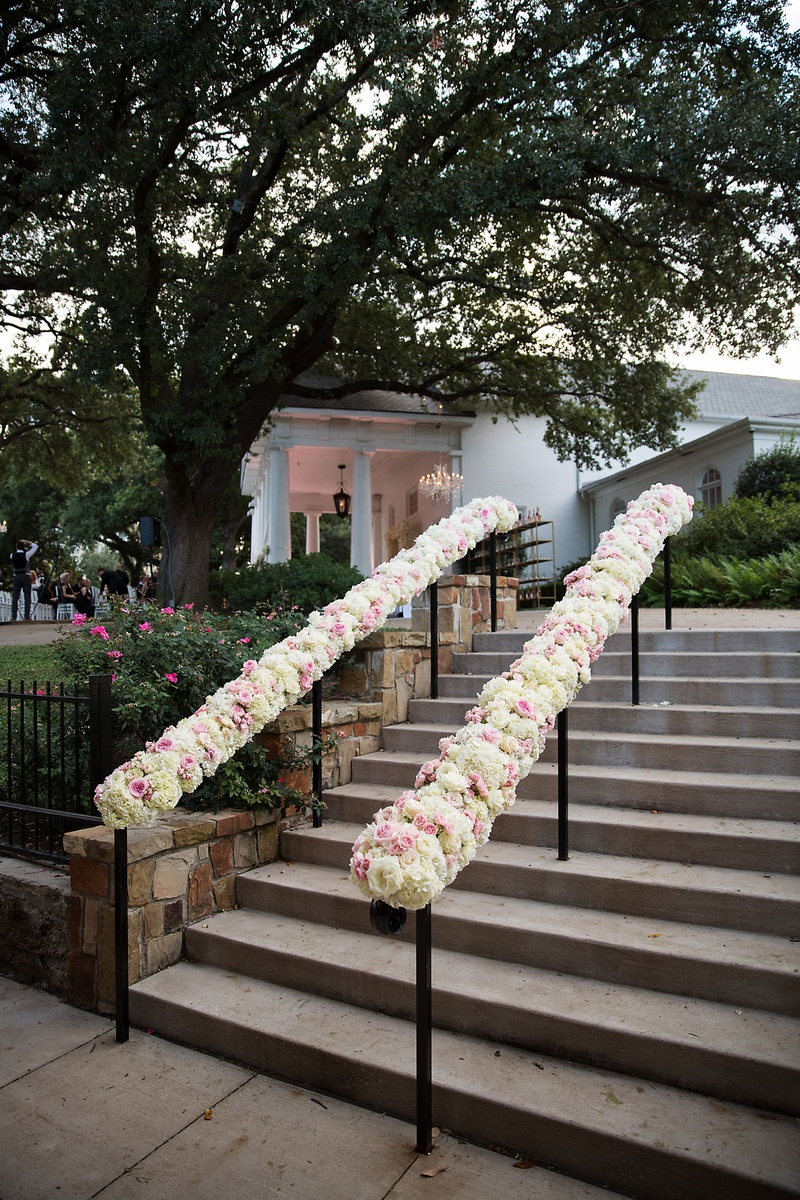 White and pink rose flowers on hand rail going up stairs at outdoor wedding venue