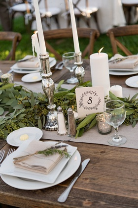 Rustic wedding reception wood table with table number in drawn wreath design, silver candlesticks