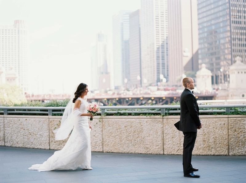 Bride sneaks up behind groom in tuxedo during first look in Chicago