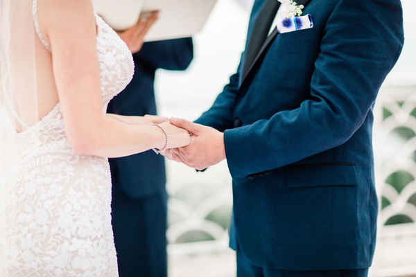 close-up of bride and groom holding hands during wedding ceremony