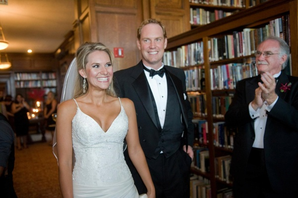 Bride in veil and a spaghetti strap gown with embroidered bodice and groom in a black tuxedo