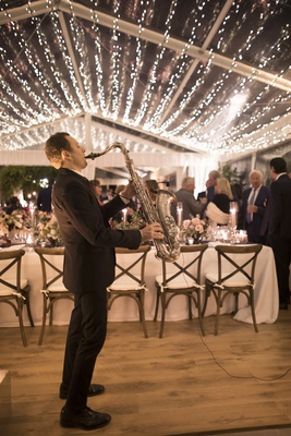 man in black suit playing saxophone during tented reception with twinkle lights covering ceiling