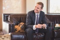 Groom smiling with dachshund-beagle doxle mix dog on leather sofa in groom's suite