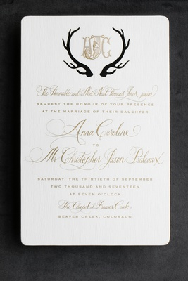 antlers in black around monogram on formal invitation