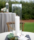 tall glass case candle white succulents greenery shells wooden chair reception décor
