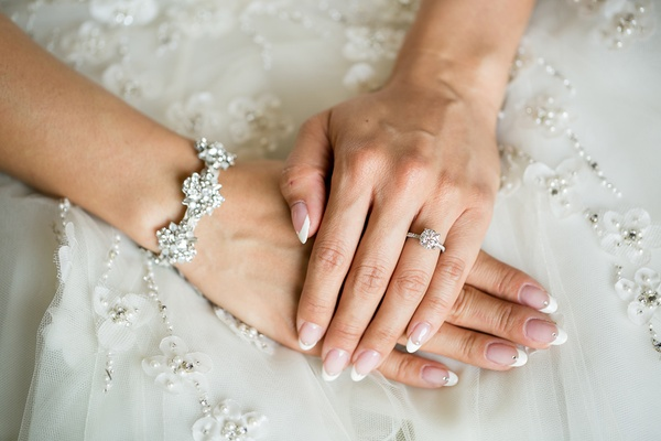 bride with almond nails, french manicure with rhinestone detail, diamond bracelet, round solitaire